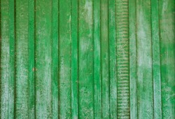 Close-up old green wooden fence with copy space. A wall of frayed wooden planks. Texture of old painted boards. Texture of old wooden planks with peeling paint. Background and texture for design.