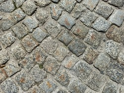 Close-up old paving stones. Cobbled street in Lviv, Ukraine. Old broken paved street. Pavement of stones. Granite cobblestones on pavement. Stone cement tile curving texture street.