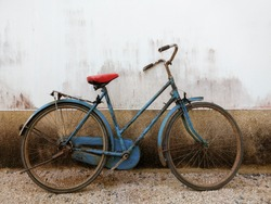 Close up old rustic blue bicycle on cement concrete wall background