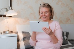 Close-up older beautiful blonde senior woman 50-60 years old sitting sofa with electronic notebook tablet. Modern technologies for older generation.