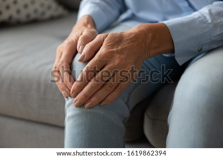 Close up older woman massaging touching knee with hands, feeling pain, mature female suffering from ache in leg, sitting on couch at home, feeling unwell, health problem concept, osteoarthritis