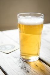 Close up on a backlit beer glass filled with a pale blonde ale, on a wood picnic table with a coaster in the background, at a local craft brewery