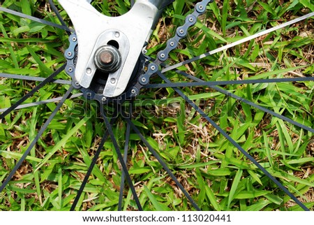 Close-up on a bicycle rear wheel on grass background