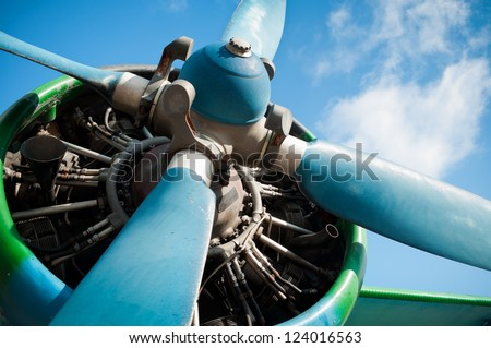 Close up on a big old, green airplane (biplane) engine with enormous propeller. Pre-focused on engine parts.