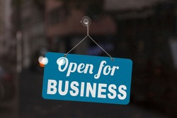 Close-up on a blue open sign in the window of a shop displaying the message: Open for business.