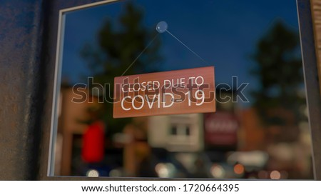 Close-up on a closed sign in the window of a shop displaying the message Closed due to Covid-19. The glass reflects the day city. 3d rendering Stock foto ©