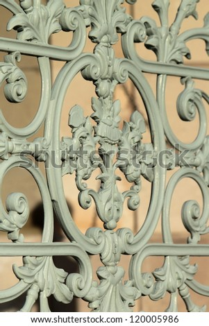 Close up on a detail of a vintage grey metallic fence in a park