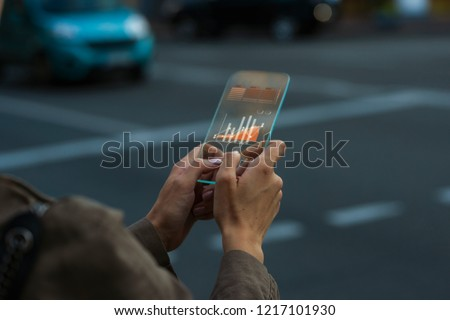 Close up on a female hand that is holding a transparent phone gadget concept, using an app with graphic chart data #1217101930