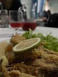 Close up on a fried fish topped by a lemon roll at a local food restaurant in Santa Cruz das Flores. Flores Island.