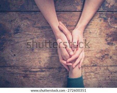 Close up on a man and a woman holding hands at a wooden table