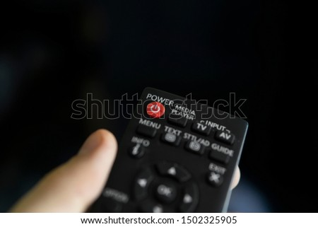 Close up on a man's hand with the remote control want switch on the TV and presses the button on the remote control. Remote control in hand closeup. #1502325905