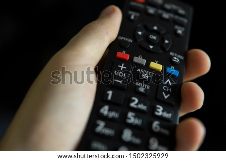 Close up on a man's hand with the remote control want switch on the TV and presses the button on the remote control. Remote control in hand closeup. #1502325929