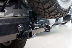 Close-up on a new black tow hitch installed on a offroad car with an iron black bumper in a vehicle repair shop. The device for the transport of the trailer in the workshop.