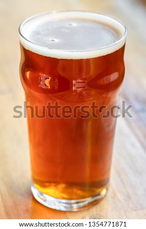 Close up on a pint of draft beer in a nonic glass, on a wooden bar at a craft brewery, with space for text on the left Stock photo ©
