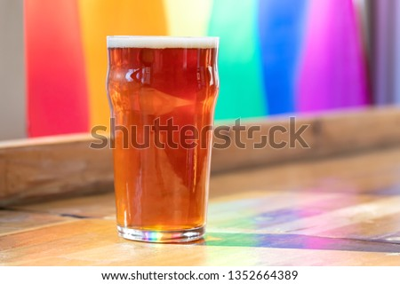 Close up on a pint of draft beer on a wooden bar with a rainbow flag background, in a LGBTQ happy hour concept, with space for text on the right Stock photo ©