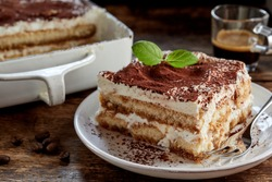Close up on a portion of gourmet tiramisu Italian dessert topped with a sprig of mint served on a plate at table in a side view