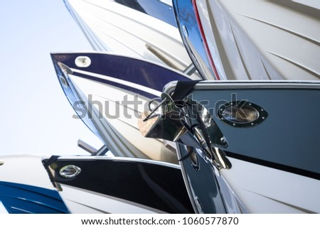 Close up on a rack of modern speedboats for sale, with pointed fiberglass hulls and bows, at a maritime storage boat yard