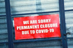 Close-up on a red closed sign in the window of a shop displaying the message