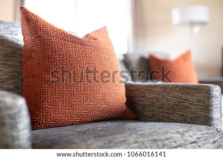 Close up on a red geometric pattern throw pillow on a gray cushioned couch in a row of chairs, with a living room scene in the blurry background, and space for text on the right #1066016141