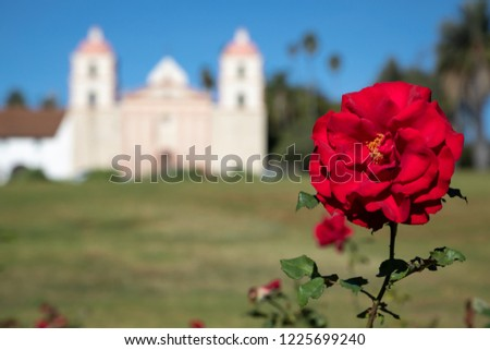 Close up on a red rose, with the Spanish style Santa Barbara Mission chapel in the blurry background, and space for text on the left #1225699240