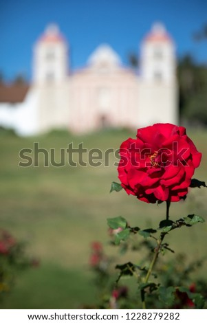 Close up on a red rose, with the Spanish style Santa Barbara Mission chapel in the blurry background #1228279282