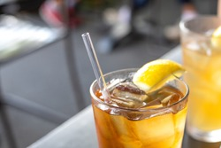 Close up on a reusable acrylic drinking straw, in a glass of ice tea