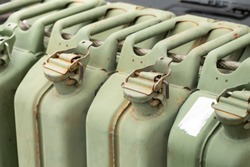 Close up on a row of old metal jerry cans, in a fuel concept