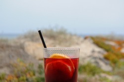 Close up on a sangria with orange and black straw on the Spanish beach