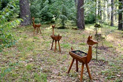 Close up on a set of wooden flower pots shaped as a herd of deer or moose standing in the middle of the forest or moor next to a dirt path od walkway seen on a sunny summer day on Polish countryside