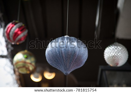 Close up on a shiny chrome and light blue ceramic Christmas ornament, suspended on fishing line and hanging from the ceiling, with colorful orbs in the blurry background #781815754