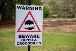 Close up on a sign reading 'Warning beware of hippo and crocodiles. There is also a visual reference to a hippo and a crocodile in a red triangle.