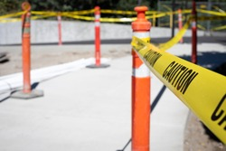 Close up on a strand of caution tape on a bollard cone, at a construction work site, with space for text on the left