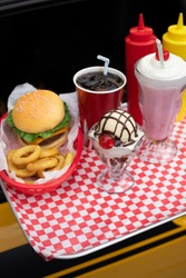 Close up on a tray of American fast food on the window of a hotrod car, in a drive-in diner concept, with space for text on bottom