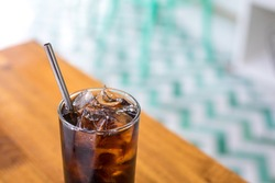 Close up on a tumbler glass full of diet cola and ice, with a reusable metal drinking straw, on a wood restaurant table