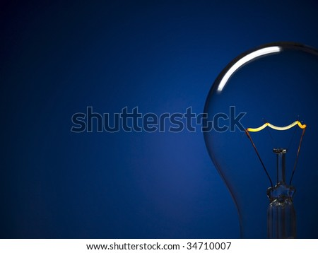 Close up on a turned on light bulb over a blue background. Copy space.