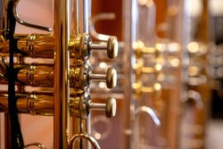 Close up on a valve section of a professional trumpet with other trumpets blurred out behind it.