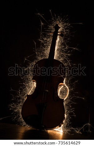 Stock Photo Close up on a violin backlit by a sparkler, background is total black