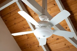 Close up on a white ceiling fan on an exposed support beam, with a vaulted wood ceiling, in the living room of a modern home, with space for text on the left