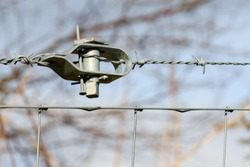 Close up on a wire tensioner holding barbedwire