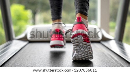 Close-up on a woman running on the treadmill at the gym.