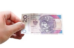 Close up on a 20 zloty banknote in a man's hand. Isolated object on white background.