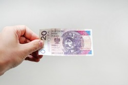Close up on a 20 zloty banknote in a man's hand. object on white background.