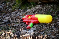 Close up on an abandoned and damaged red, yellow and green toy gun laying among dry and withered leaves in the middle of a forest or moor seen on a spring day during a hike on a Polish countryside