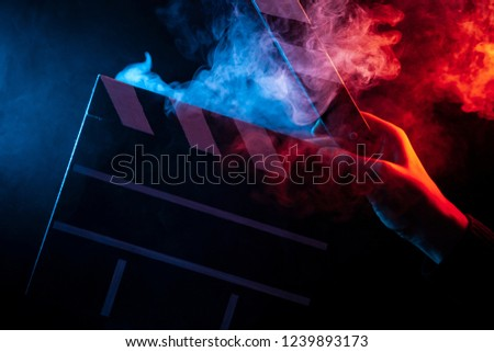 Photo of  Close-up on an open clapperboard in hand before starting shooting a film with multi-colored smoke around with red and blue backlighting on a black isolated background