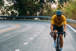 Close up on Asian man wearing a yellow cycling jersey, who's riding a road bike up high on hill in the morning. Under morning sunshine with determination on his face.