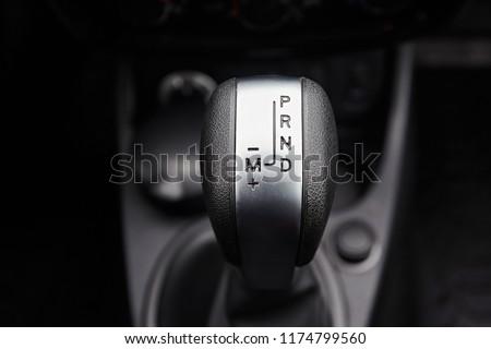Close-up on automatic transmission lever in modern car. Car interior details. Transmission shift. #1174799560