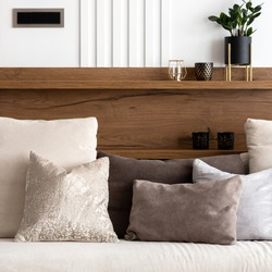 Close-up on beige sofa with decorative pillows, wooden wall with shelf and white molding on the wall