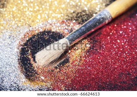 Close-up on brush and shining powder. Very shallow focus on tip of the brush.