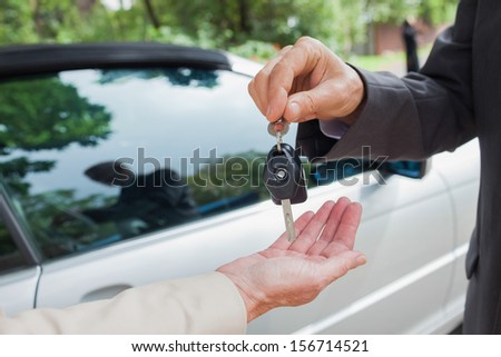 Close up on business man giving his keys to his partner to go to a meeting