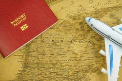 Close up on Canada map with passport and toy aircraft. Travel concept. Canada is a country in the northern part of North America.